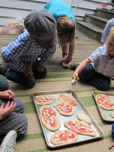 Henri decorating the pizza's
