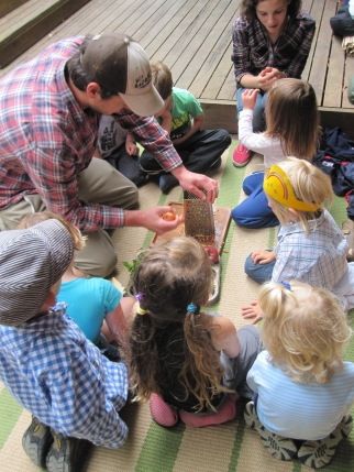 The children gather to see what Greg is putting in the salad!
